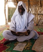 """[Imam Kura Nguigmibe reading while seated before a copy of """"Argumentaire islamique sur l'équité de genre""""]"""